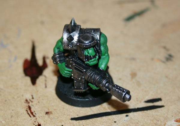 Once I have drybrushed the metal parts I use a dark green base for the Ork skin.