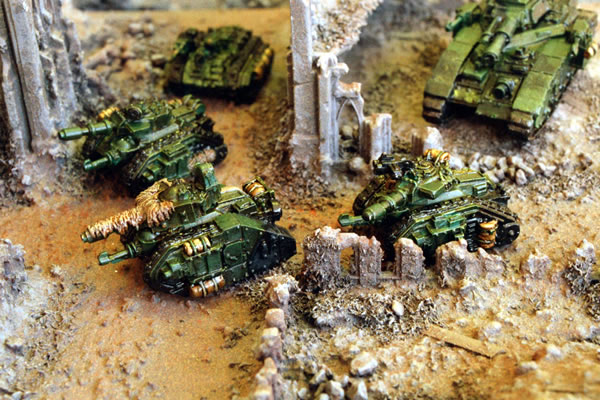 Imperial Leman Russ tanks supported by Chimeras and a Baneblade move through the ruins of an Imperial City.